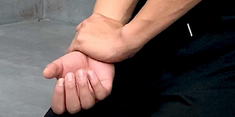 鍛えてたい腕の手首に反対の手をあてる